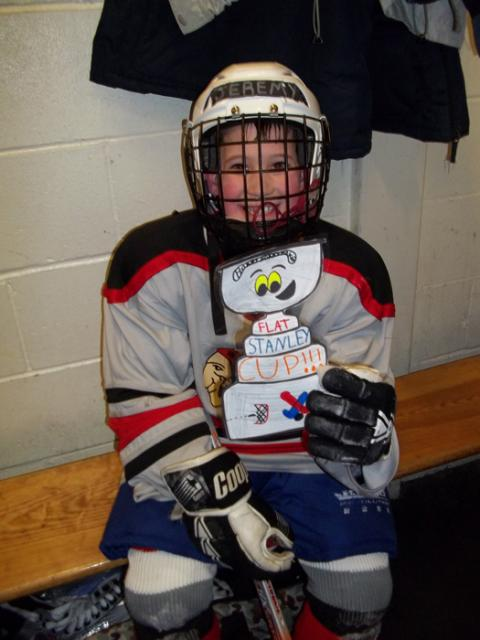 With Ash-West Warrior Jeremy Hansen, Flat Stanley Cup takes in the sights (and smells) of the locker room at the NESC.: Photo submitted by Kelly Hansen