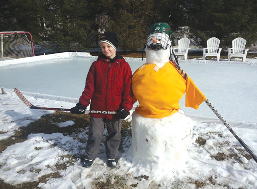 8-year-old William Ogden and his snowy wingman enjoy hours on their backyard rink.