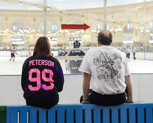 Proudly sporting her son's number on the back of her jersey, Susan Kowalenko takes a break from the Qatar heat with her husband, Marlin Peterson, to support Zack as he hits the ice with his team.