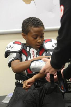 Daihauon Brooks-James gets help with his equipment. The camp offered many of the kids the opportunity to put on hockey gear for the first time.