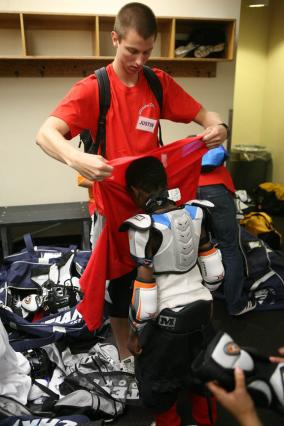Mohamed Abdirmahn gets help with his gear from volunteer Justin Jenson