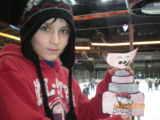 Spencer Wright takes his Flat Stanley Cup to a Charolette Checkers game. The Checkers went on to win in a shootout and Flat Stanley made it on the big screen twice with his game-winning smile.: Photo submitted by Jill Wright