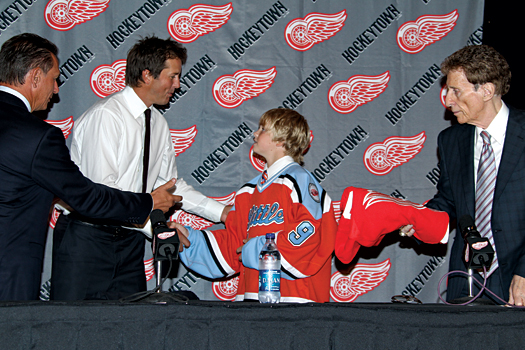 Mike Modano receives his new Detroit Red Wings jersey from Little Caesars AAA player Drake Rymsha during an Aug. 6, 2010 press conference.