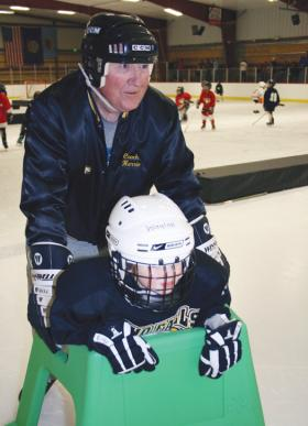 Waylon Muirbrook leans on a skate support as he learns to ice skate. Bill Harrie glides right along with him talking him out of his tears.
