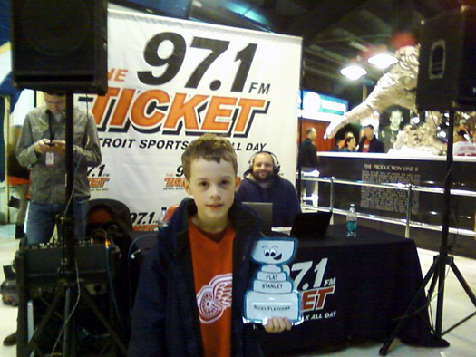 Ricky Fletcher holding Flat Stanley in front of the WDFN 97.1 Detroit's Ticket radio station's table at Joe Louis Arena.: -Photo submitted by Connie & Ricky Fletcher