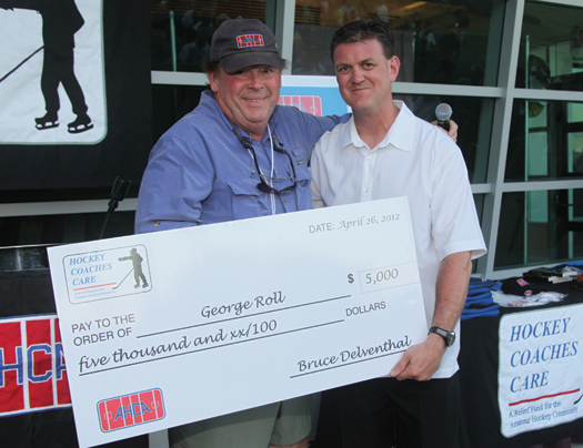 USA Hockey&amp;rsquo;s Scott Paluch presents a check to George Roll on behalf of Hockey Coaches Care.