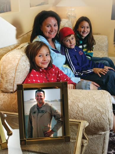 Janice Harmon and her children, Kellie, Matthew and Jodie sit on the couch of their Monument, Colo., home with a photo of father and husband Lt. Col. Steve Harmon close by.