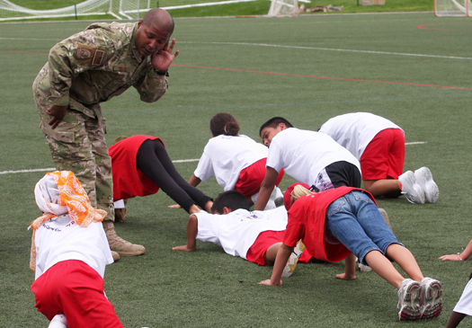 Army Sgt. Rob Blue helps the campers with their push-ups.