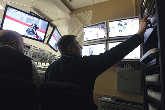 Doug Grebenc, a member of the Colorado Avalanche off-ice crew, checks the feed in the video review booth.