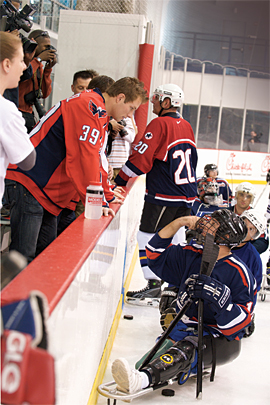 David Steckel of the Washington Capitals talks with sled hockey player Michael Caine