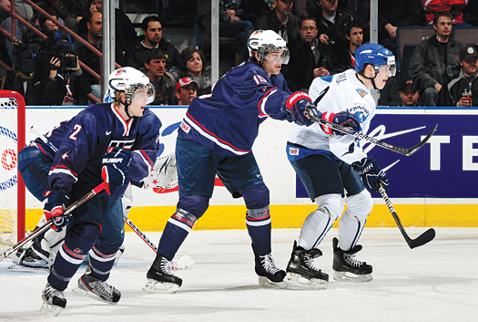 USA's Jon Merrill (15) battles with Finland's Simo-Pekka Riikola while Austin Czarnik (2) looks on during preliminary round action at the 2012 IIHF World Junior Championship.