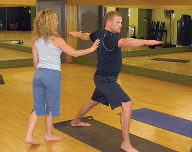 "Yoga instructor Dana Edison helps Boston Bruins goaltender Tim Thomas find his inner warrior in yoga's ""Warrior II"" pose."