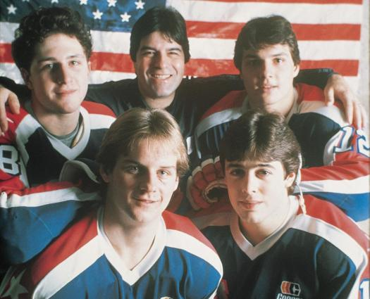 Lou Vairo, head coach of the 1984 U.S. Olympic Team, is surrounded by members of the Diaper Line, including Ed Olczyk (right), Pat Lafontaine (bottom right), David A. Jensen (bottom left) and defenseman Al Iafrate.