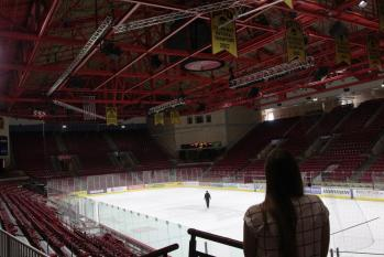 Kelsey stares out at the Pioneers' ice surface, with the team's 2017 National Championship banner hanging in the background