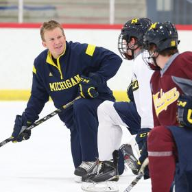 In addition to finishing his degree, Mike Komisarek working as an under-graduate assistant coach, sharing his experience with Michigan hockey players.